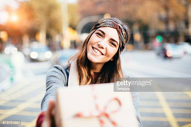 young beautiful woman handing a present. - geben stock-fotos und bilder