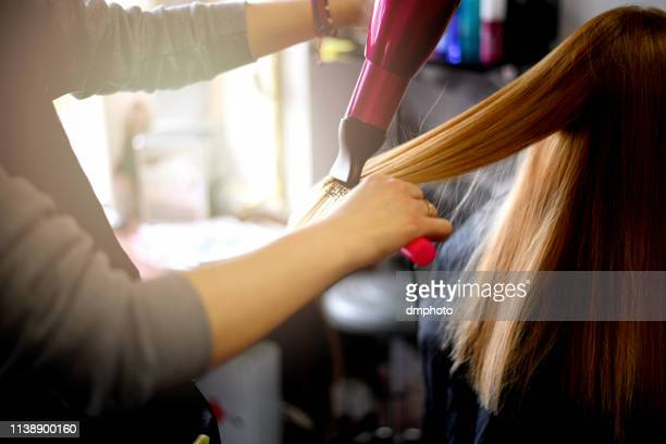 young beautiful woman having her hair dried at hair salon - blow drying hair stock pictures, royalty-free photos & images