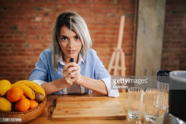 jeune belle femme retenant un couteau de cuisine - pointu photos et images de collection