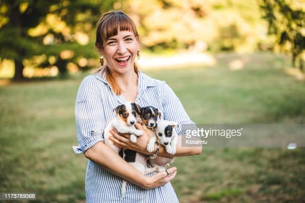 公共の公園でジャックラッセル子犬を抱きしめる若い美しい女性 - 動物調教師 ストックフォトと画像