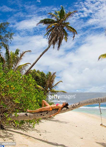 Young beautiful woman in a bikini lying on a palmtree at white sandy Banana Beach on September 27 2015 in La Passe La Digue Seychelles