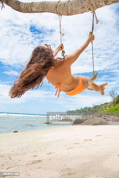 Young beautiful woman in a bikini swinging at a palmtree at white sandy Banana Beach on September 27 2015 in La Passe La Digue Seychelles