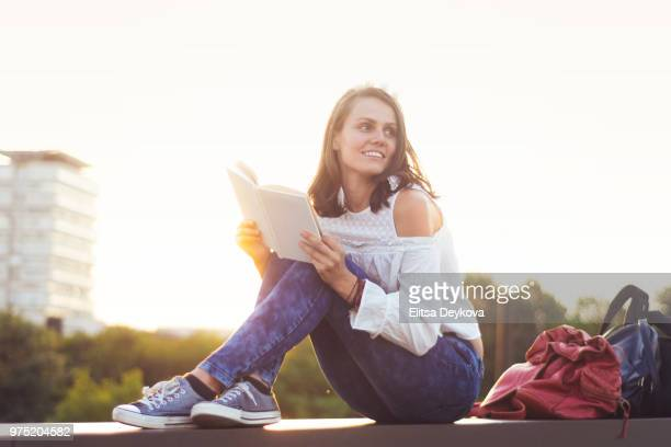 Young beautiful woman in a city with a book in hands