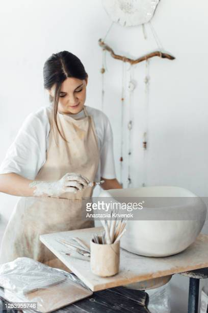 young beautiful woman in dirty apron making handmade pottery using special equipment while working in light white studio. small business at home. - 工芸品 ストックフォトと画像