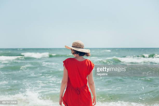 young beautiful woman in front of the sea in red dress and straw hat standing back to the camera looking down - odessa ukraine stock pictures, royalty-free photos & images