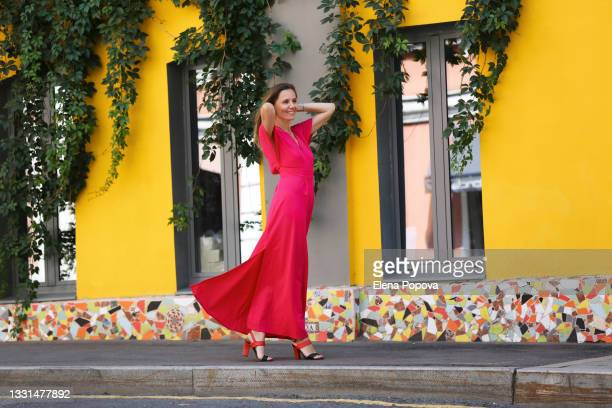 young beautiful woman in long pink dress walking on the street - dress stock pictures, royalty-free photos & images