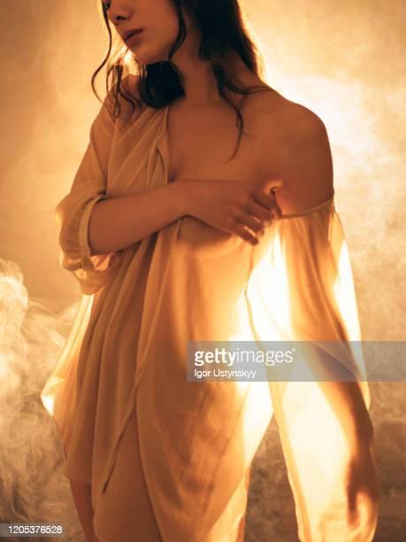 young beautiful woman in orange mist - real body fotografías e imágenes de stock