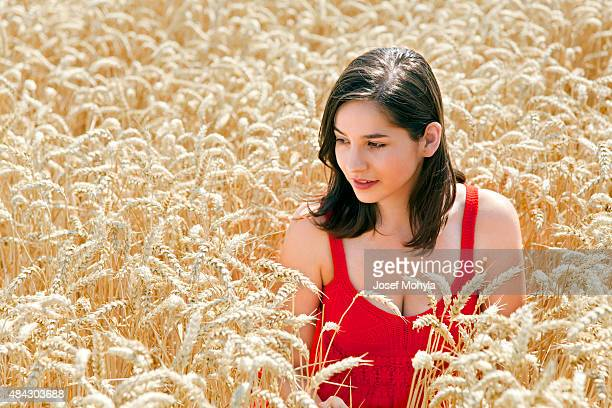 Young beautiful woman in the middle field of wheat