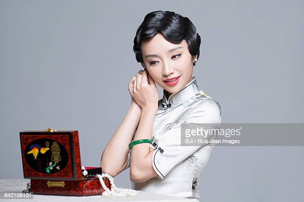 Young beautiful woman in traditional cheongsam dressing up herself