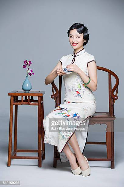 Young beautiful woman in traditional cheongsam drinking tea