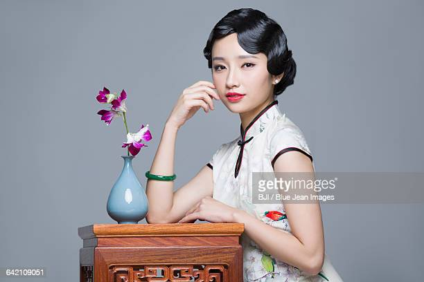 Young beautiful woman in traditional cheongsam with orchid