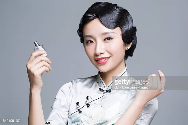Young beautiful woman in traditional cheongsam with perfume
