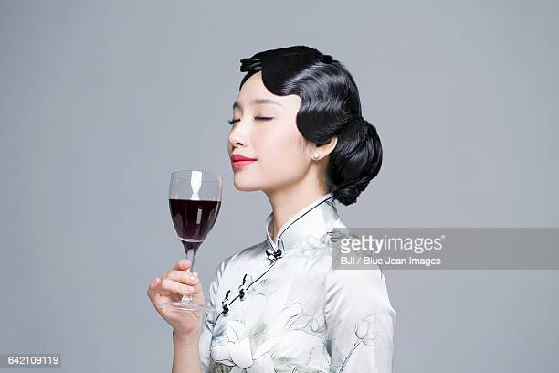 Young beautiful woman in traditional cheongsam with red wine