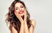 Young, beautiful woman is looking straight on viewer with wide, happy smile. Human emotions.