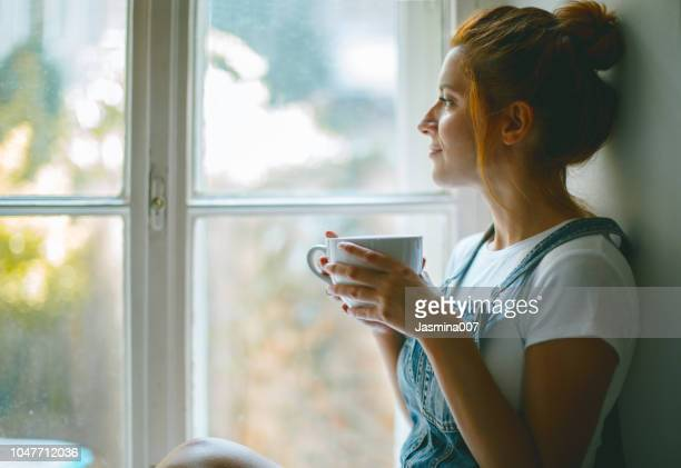 young beautiful woman is looking through the window and drinking coffee in the morning - gente serena foto e immagini stock