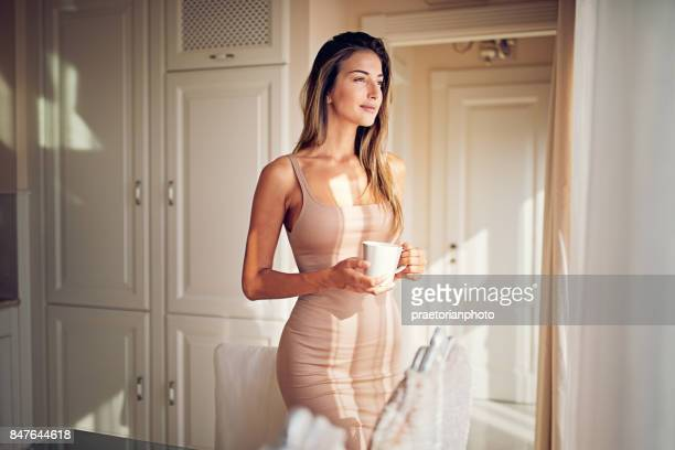 Young ,beautiful woman is looking through the window and drinking coffee in the morning