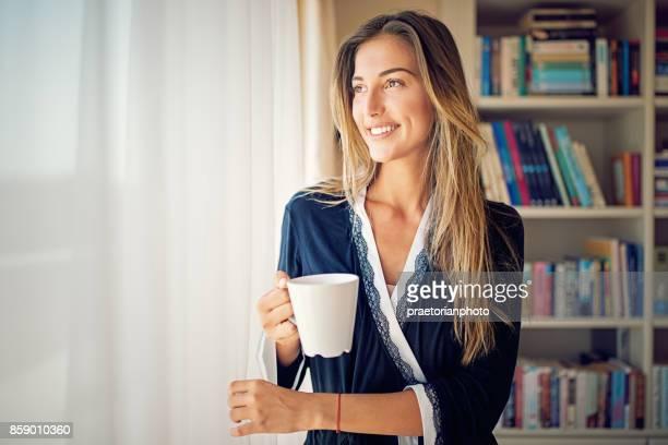 Junge, schöne Frau ist durch die Fenster schaut und Kaffeetrinken am Morgen