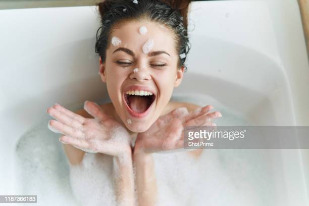 young beautiful woman is lying in the bathroom with foam and playing with foam and bubbles - femme dans son bain photos et images de collection
