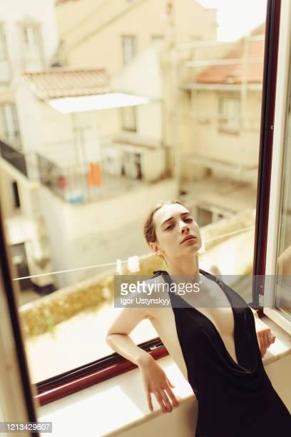 young beautiful woman leaning on window sill - solo una donna giovane foto e immagini stock