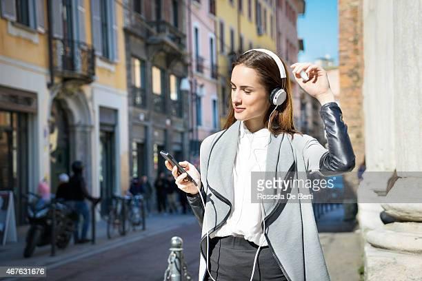 Joven hermosa mujer escuchando música y bailando