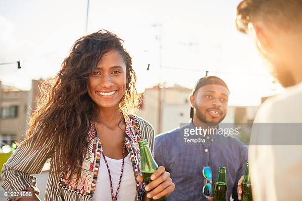 Young beautiful woman looking at camera and holding beer bottle