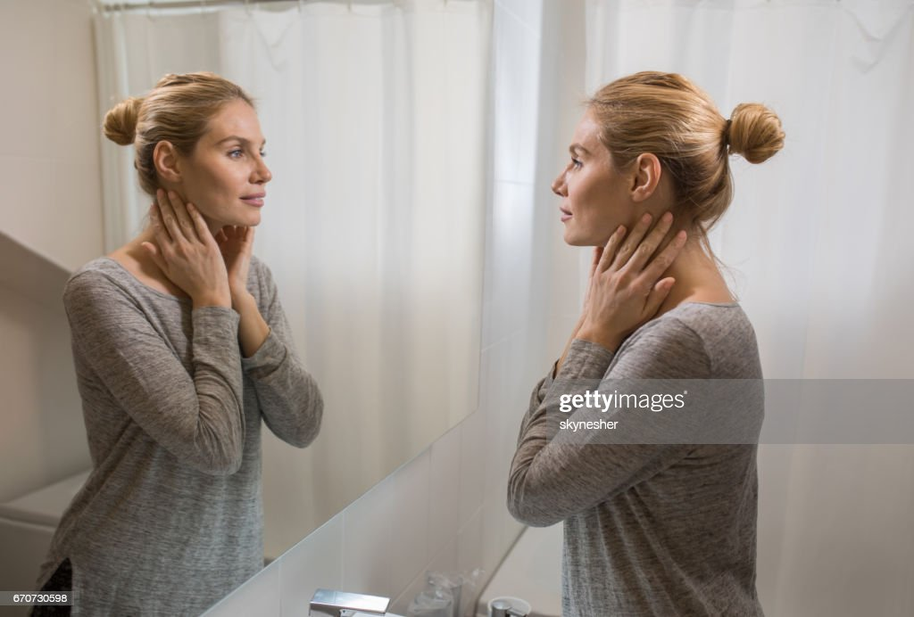 Young beautiful woman looking herself in the mirror at bathroom. : Stock Photo