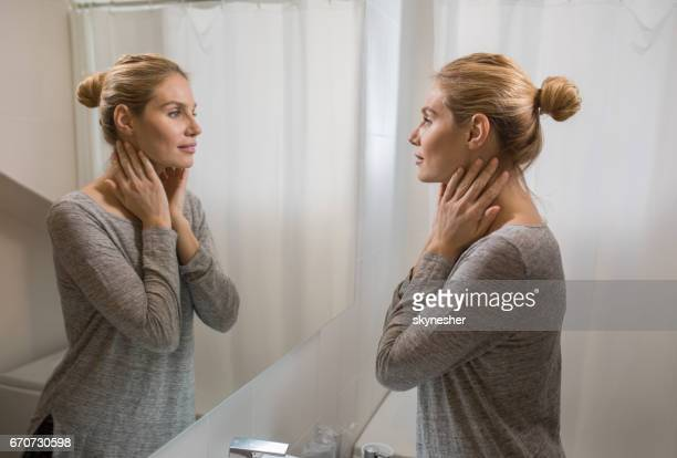 young beautiful woman looking herself in the mirror at bathroom. - mirror stock photos and pictures