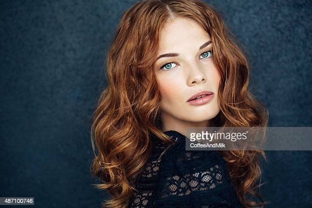 young beautiful woman on dark background - redhead stock pictures, royalty-free photos & images