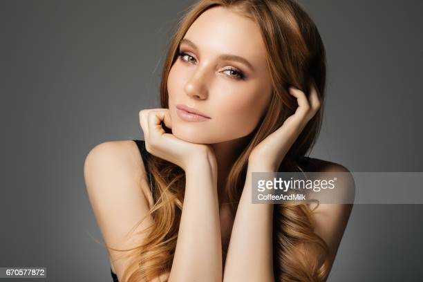 Young beautiful woman on light background