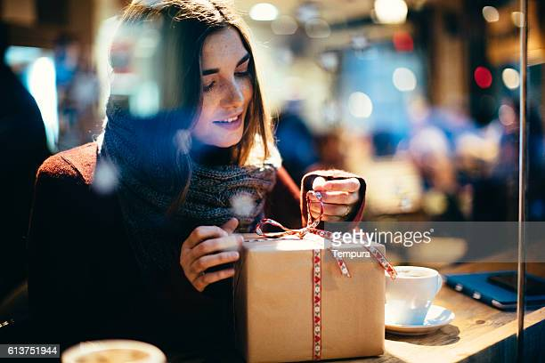 young beautiful woman opening a present. - birthday gift stock pictures, royalty-free photos & images