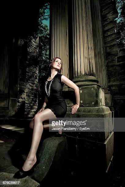 Young Beautiful Woman Posing While Leaning Against Columns