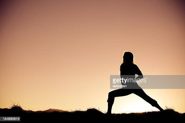 Young beautiful woman practicing yoga at sunset