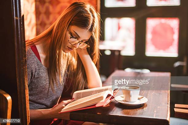 Young beautiful woman reading a book in a cafe.