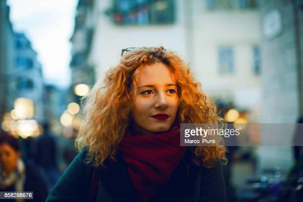 junge schöne frau rothaarige zu fuß in die stadt - introspektion stock-fotos und bilder