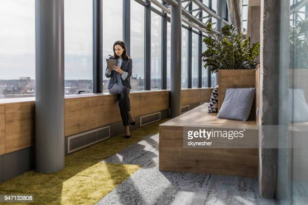 young beautiful woman relaxing in a hallway of an office building and using touchpad. - economist stock pictures, royalty-free photos & images