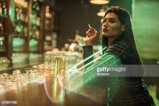 Junge schöne Frau sitzt am bar-Theke und Rauchen.