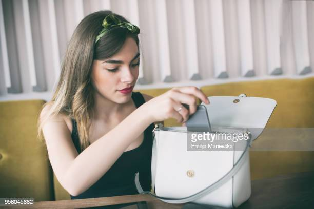 young beautiful woman sitting in restaurant and checking her purse - borsetta da sera foto e immagini stock
