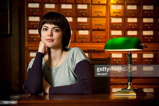 Young beautiful woman sitting in the library card index