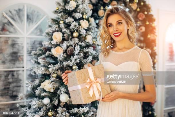 jonge mooie vrouw zat naast de kerstboom - versierde jurk stockfoto's en -beelden
