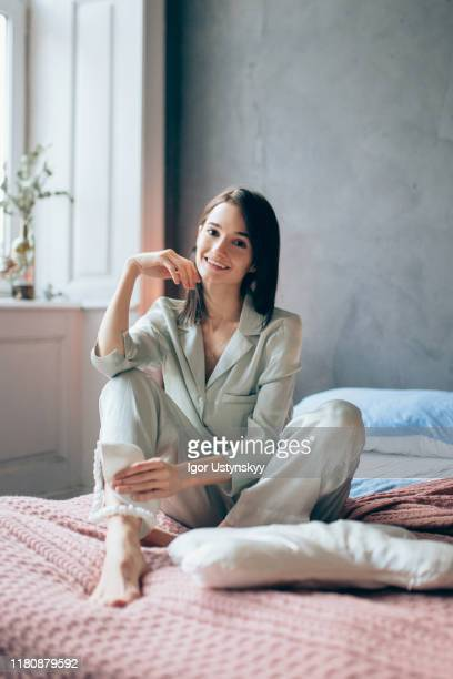 young beautiful woman sitting on bed - silk stock pictures, royalty-free photos & images