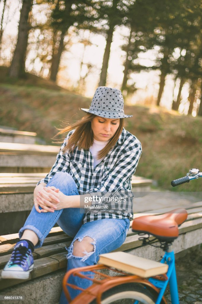 Young beautiful woman sitting on bench in park. Nature environment background. : Stock Photo
