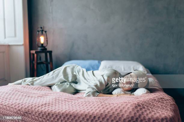 young beautiful woman sleeping in bed - silk stock pictures, royalty-free photos & images