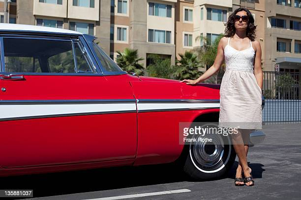 young beautiful woman standing beside a red car