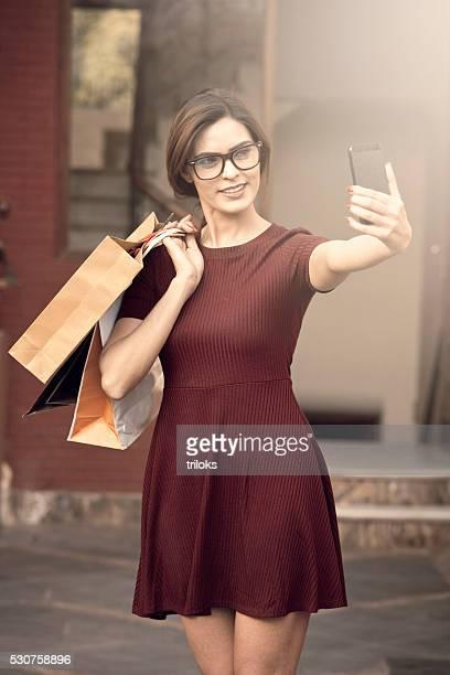 Jovem e Bela mulher tendo uma selfie e compras