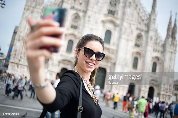 Joven hermosa mujer tomando autofoto en frente del Duomo de Milán