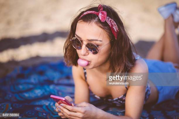 Young beautiful woman texting and blowing a bubble gum