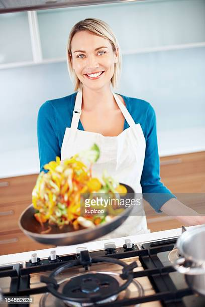 Young beautiful woman tossing food in a frying pan