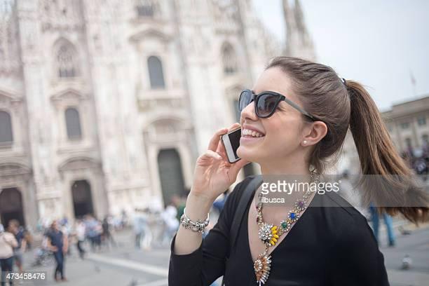 Joven hermosa mujer usando el teléfono en la parte frontal del Duomo de Milán