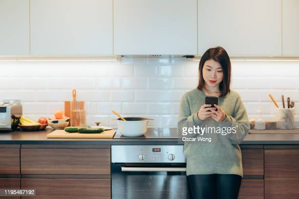 young beautiful woman using phone standing and leaning on kitchen worktop - standing stock pictures, royalty-free photos & images