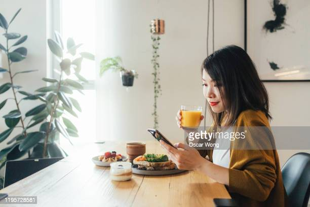 young beautiful woman using phone while having breakfast - only young women stock pictures, royalty-free photos & images